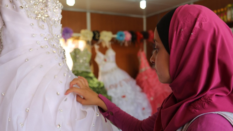 14 year old Hala * looks at wedding dresses in Za'atari Camp.